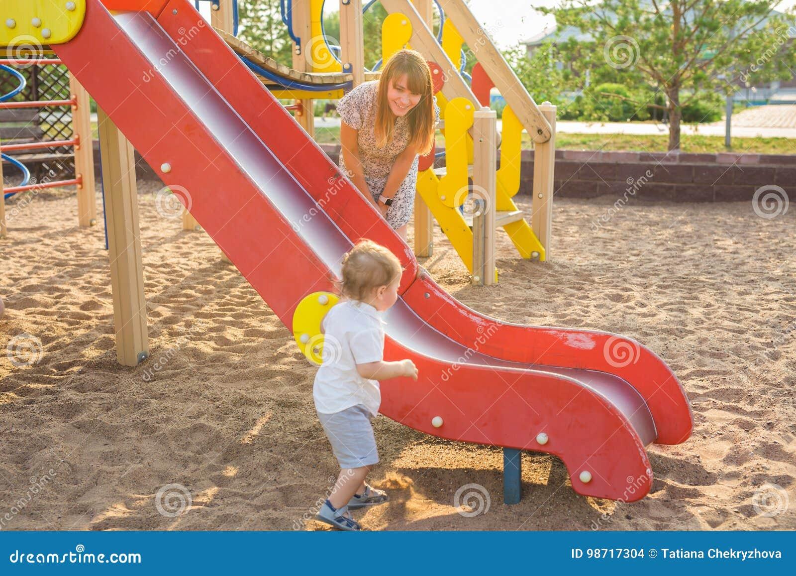 Das glückliche Freien des kleinen Jungen im Spielplatz mit seinen Eltern