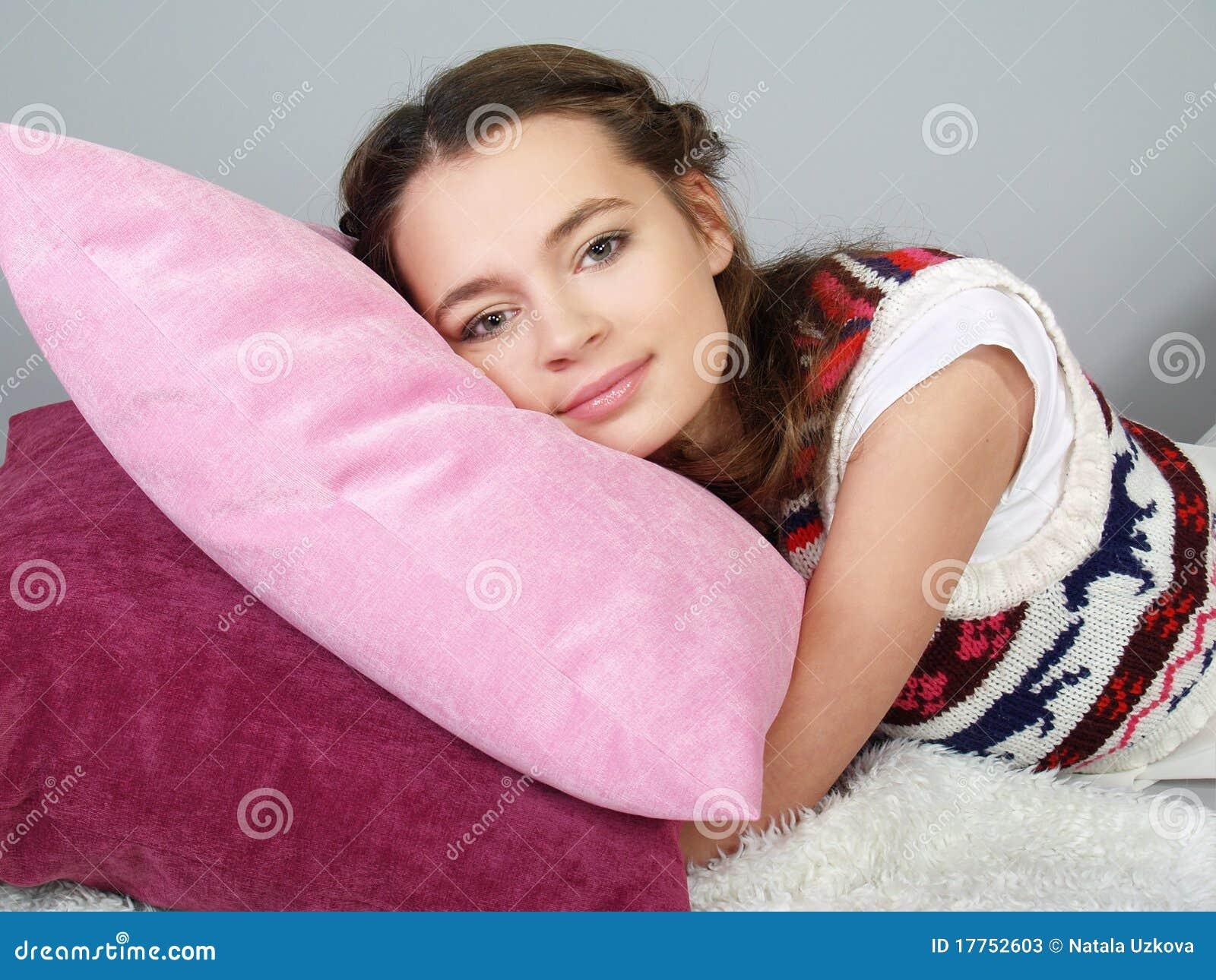 Das glückliche schöne Mädchen liegt auf rosafarbenen Kissen