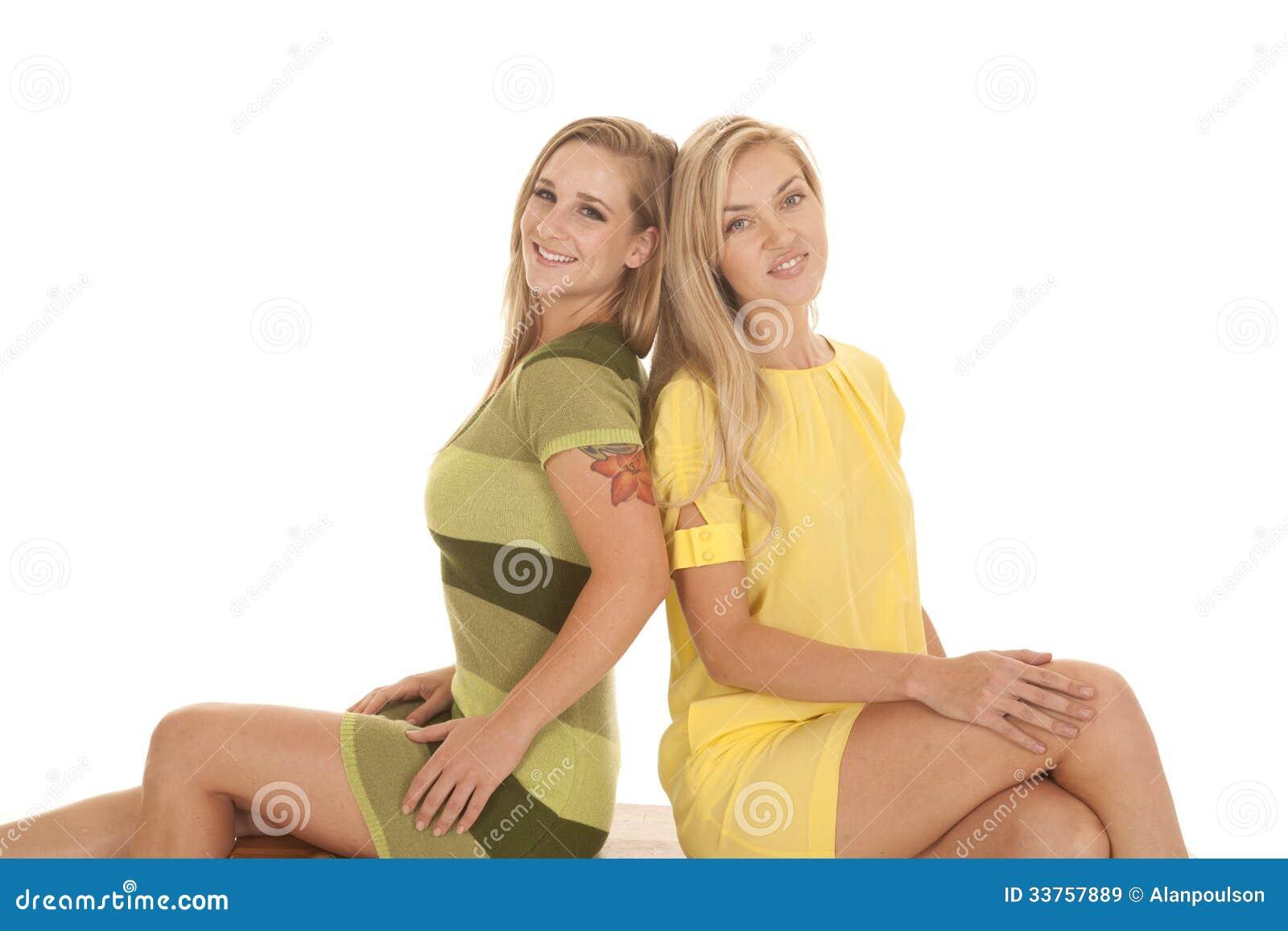 Das grüne Gelb von zwei Frauen sitzen Lächeln