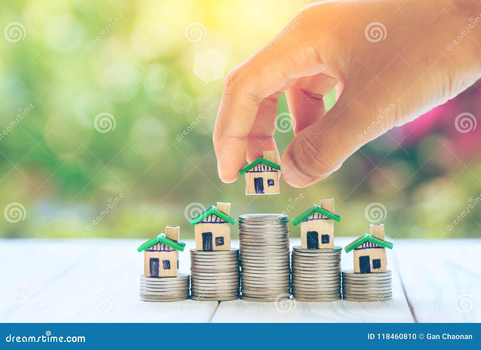 Das Haus, das auf Münzen Männer ` s Hand gesetzt wird, plant Einsparungensgeld von Münzen, um ein Hauptkonzeptkonzept für Eigentu