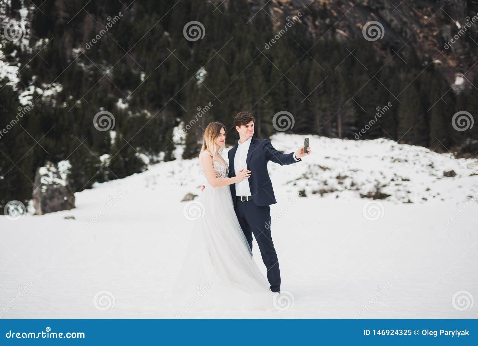 Das junge glückliche Paar, das ein selfie macht, Berge gestalten im Schnee auf dem Hintergrund landschaftlich
