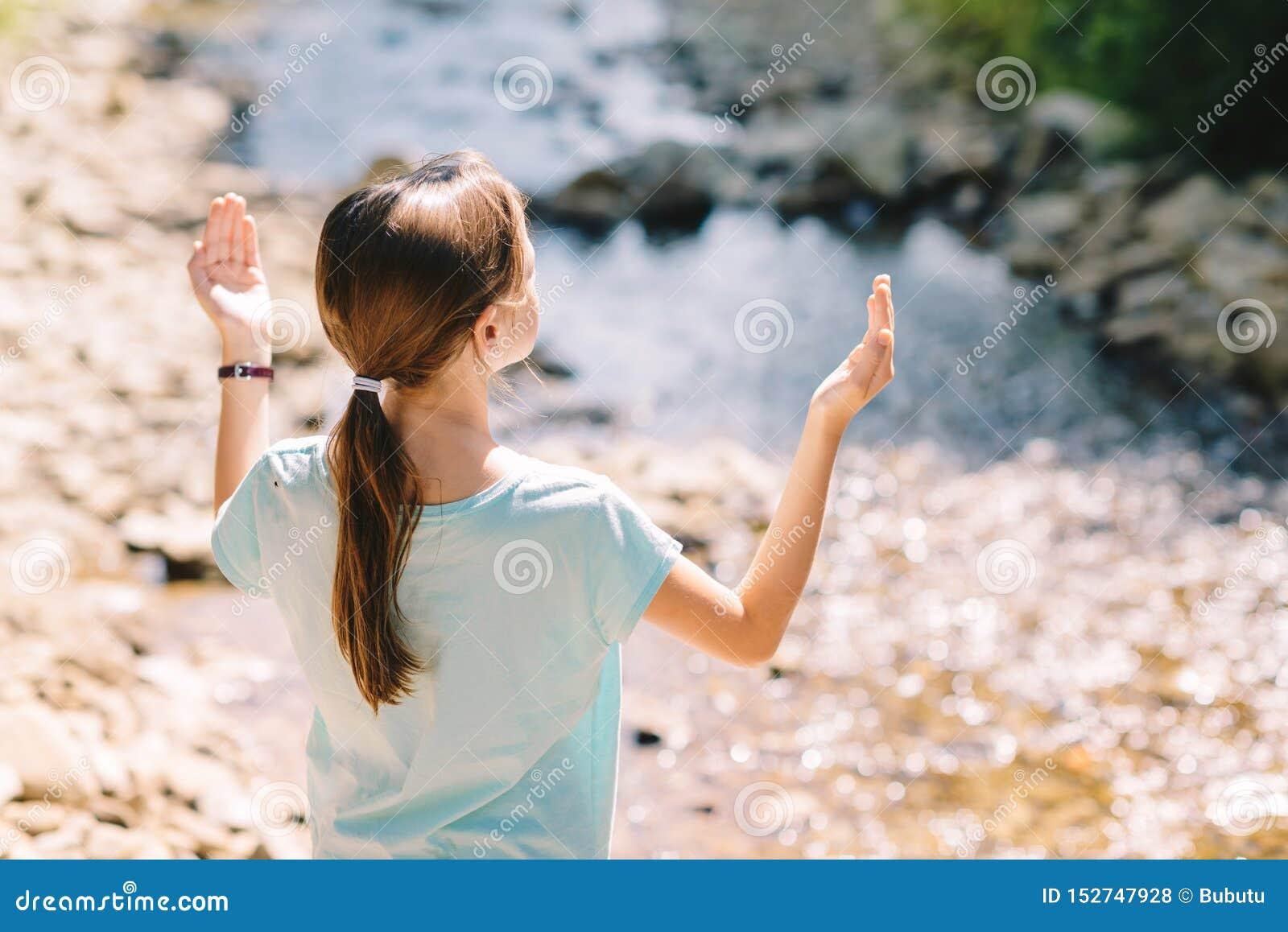 Das junge Mädchen hebt ihre Arme betend auf den Banken eines Gebirgsstromes an
