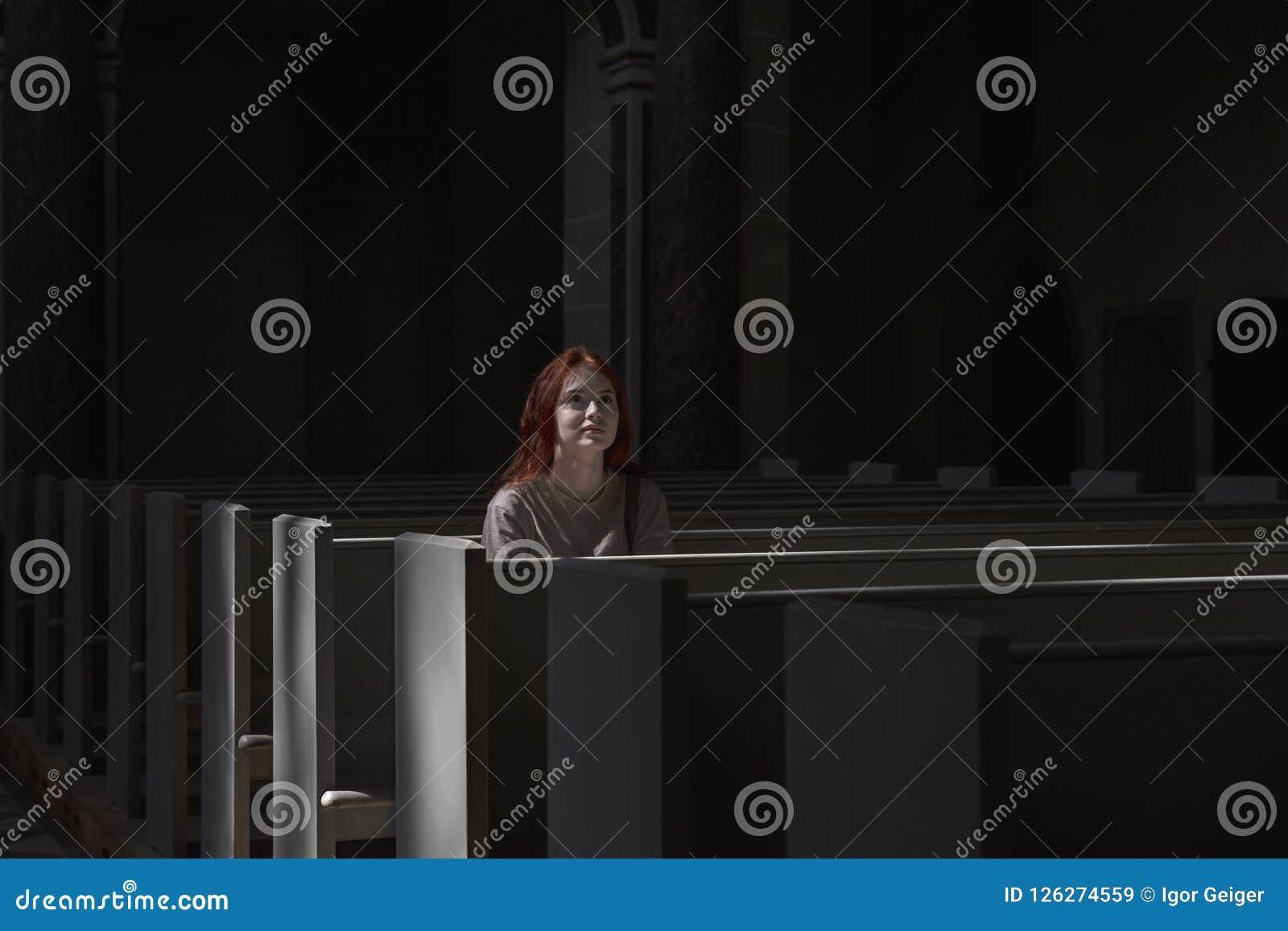 Das junge schöne rothaarige Mädchen, das einsam ist, sitzt in der Kirche, die zu betet