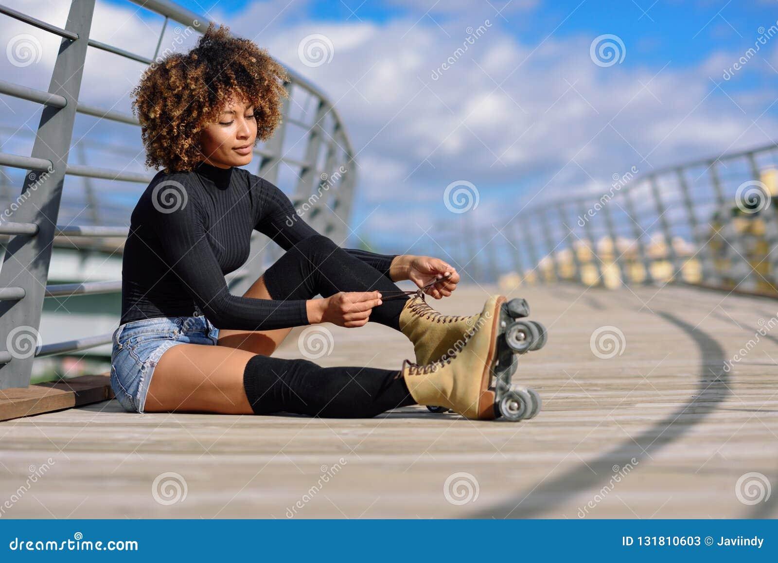 Das junge schwarze Mädchen, das auf städtischer Brücke sitzt und setzt an Rochen Frau mit der Afrofrisur, die am sonnigen Tag rol