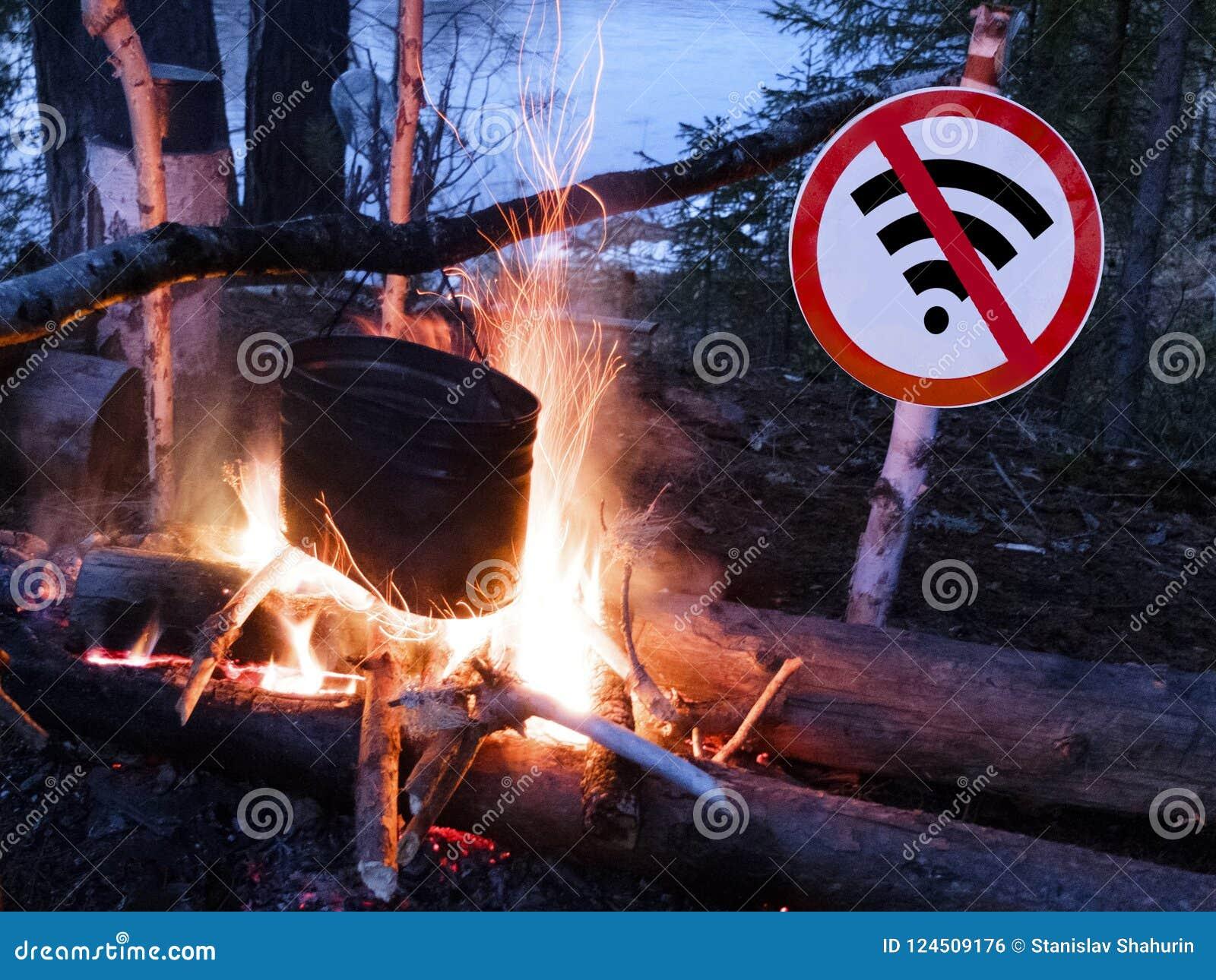 Das kein wifi Zeichen nahe dem Feuer und dem Topf auf dem Strand digitales Detoxkonzept und -bruch von der Technologie