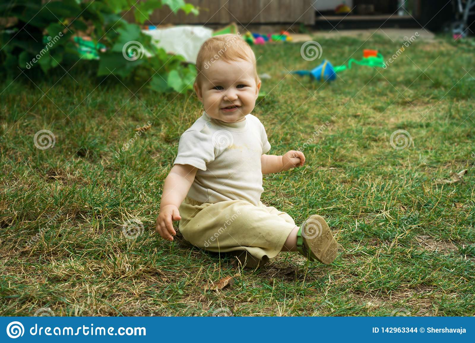 Das Kind glücklich kriecht und sitzt auf dem grünen Gras Kleinkindlächeln und -verschiebung auf allen fours um das Yard im Freien