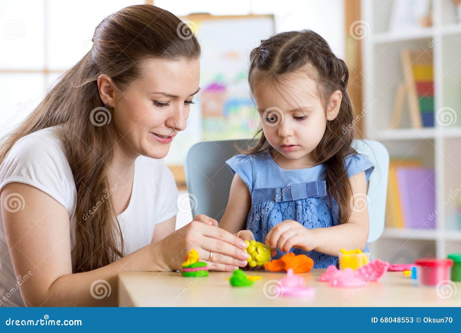 Das Kindermädchen und -frau, die bunten Lehm spielen, spielen an der Kindertagesstätte oder am Kindergarten