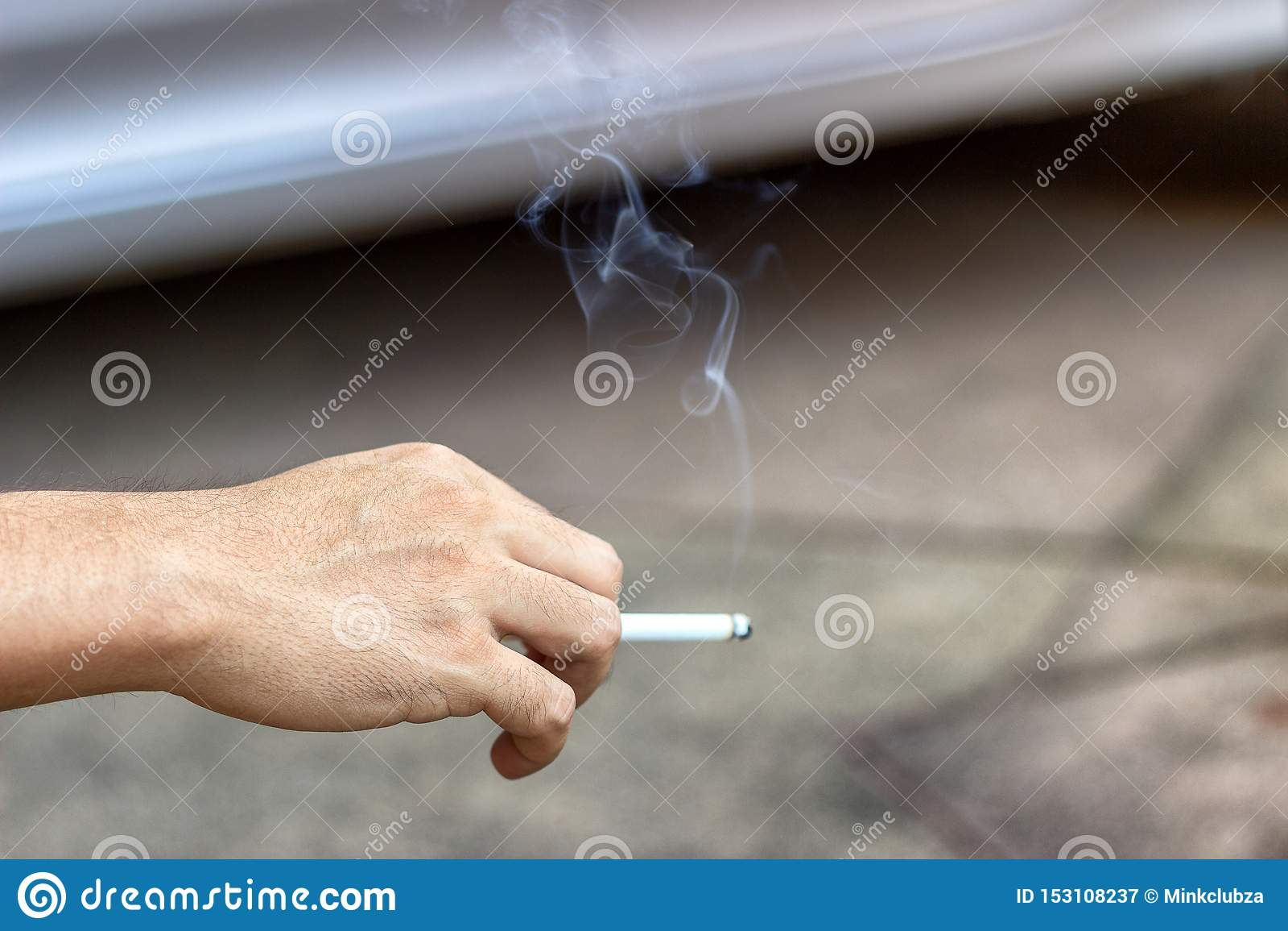 Das Konzept der rauchenden Einstellung mit den männlichen Händen trägt Rauchzigarettendrogen, die zu den Leuten herum schädlich s