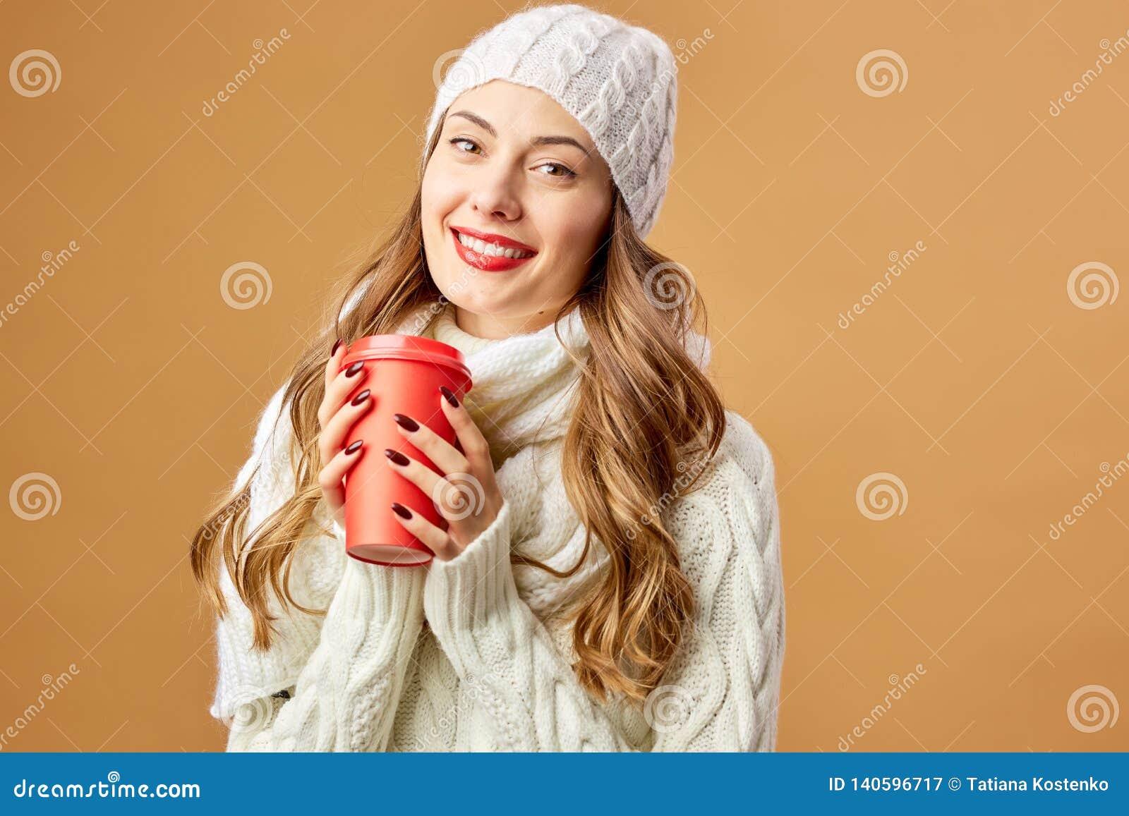 Das lächelnde Mädchen, das in der weißen gestrickten Strickjacke und im Hut gekleidet wird, hält eine rote Schale in ihren Händen
