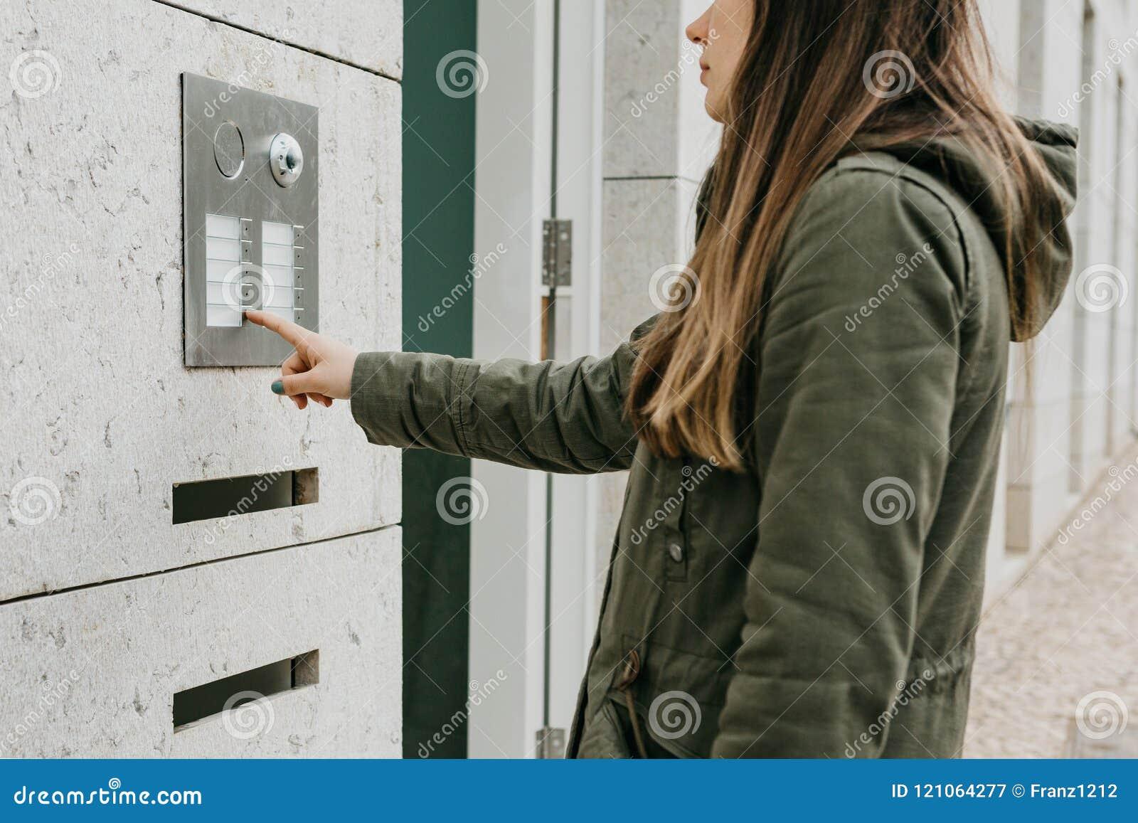 Das Mädchen betätigt den doorphone Knopf oder nennt die Wechselsprechanlage