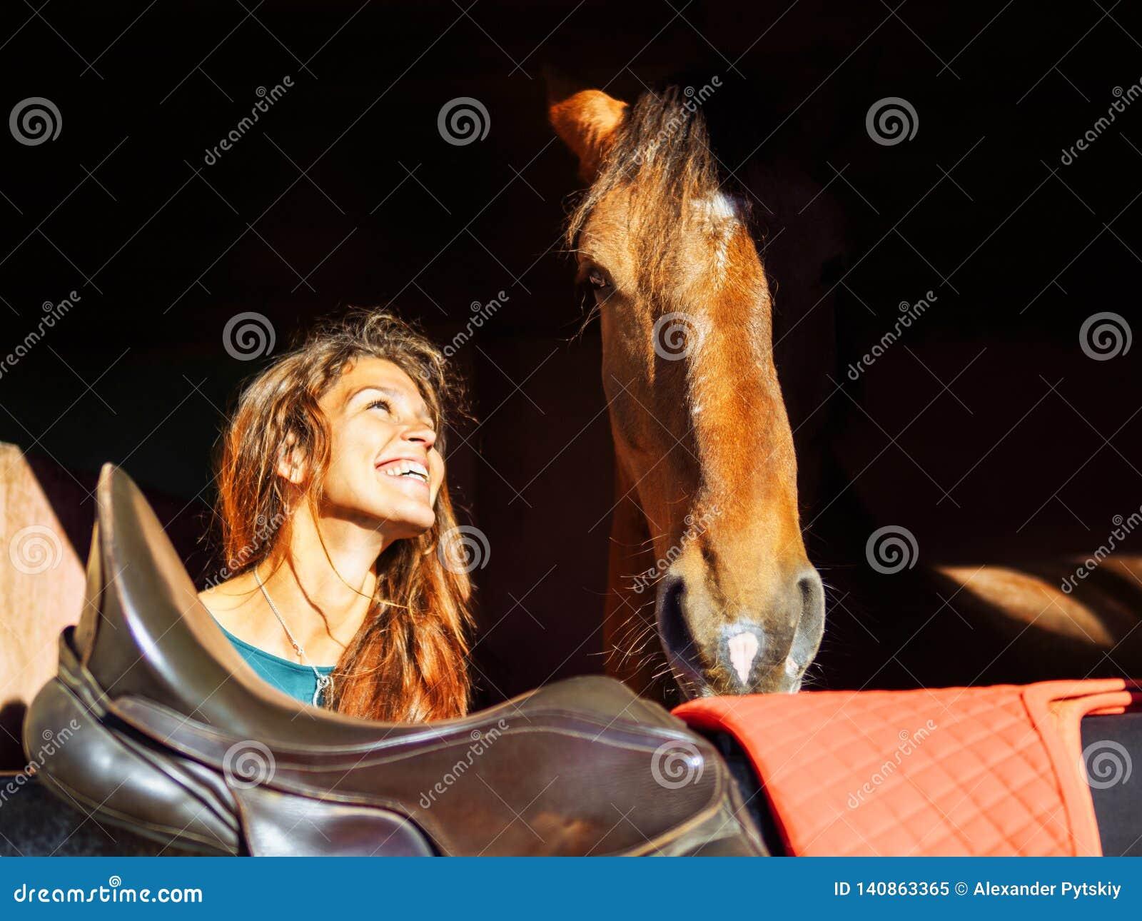 Das Mädchen betrachtet den Kopf eines roten Pferds mit Liebe