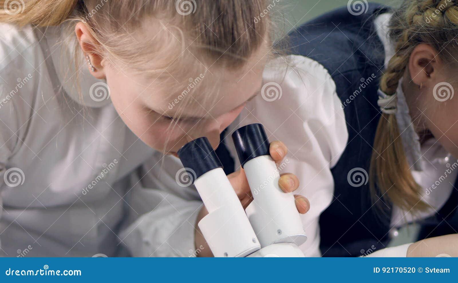 Das mädchen das im mikroskop macht wissenschaftsexperiment schaut