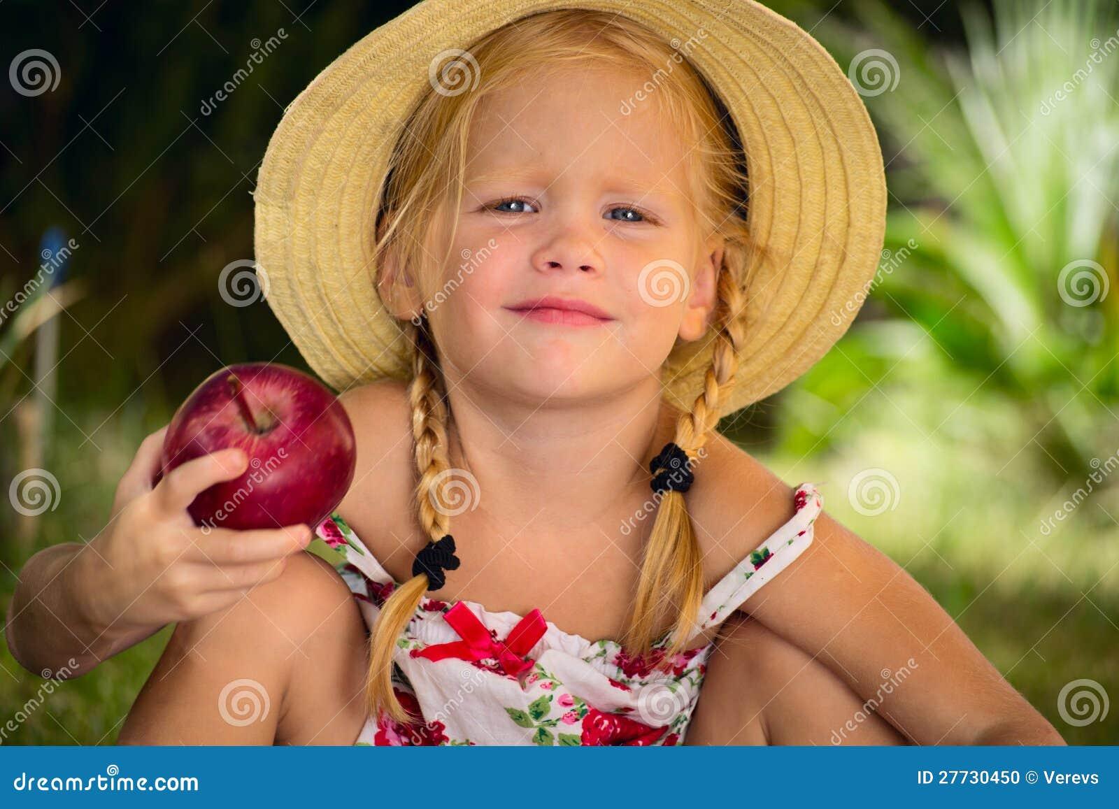 Das Mädchen in einem Hut mit rotem Apfel