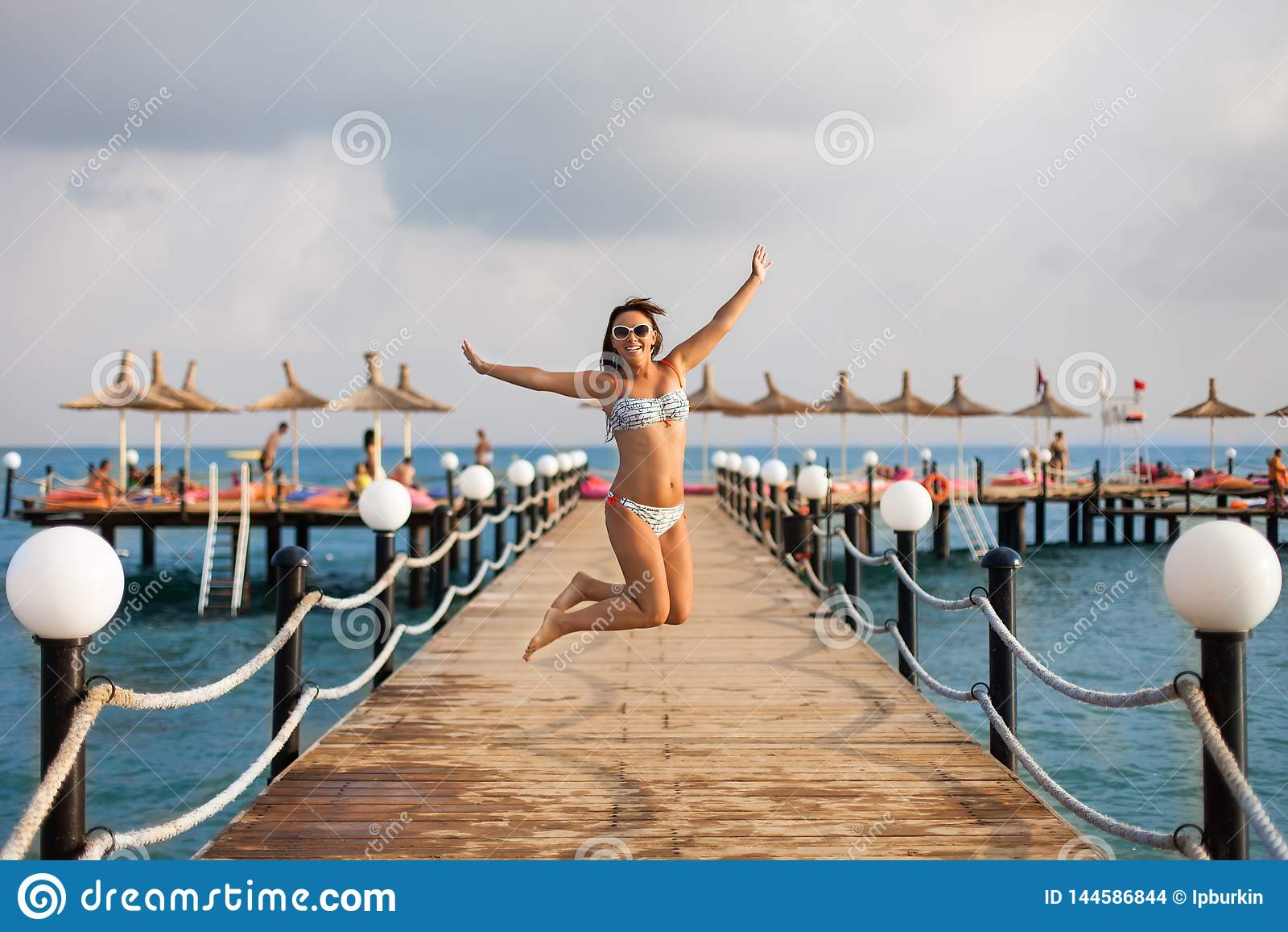 Das Mädchen im Badeanzug sprang auf den Pier Glückliches Mädchen auf dem Pier Getrennt auf Schwarzem Das reizend Mädchen, das auf