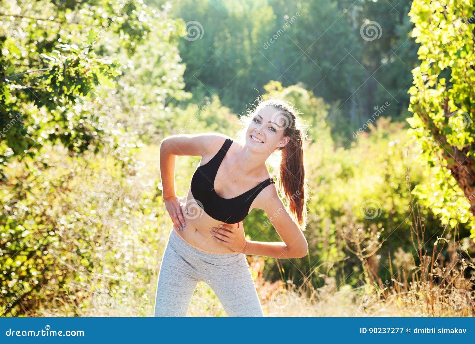 Das Mädchen ist engagierte Eignung in einem Wald bei Sonnenuntergang