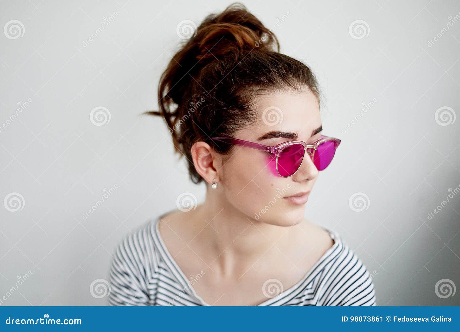 Das Mädchen lächelt glücklich in den rosa Gläsern Eine naive Ansicht der Welt im Übergang zum Erwachsensein
