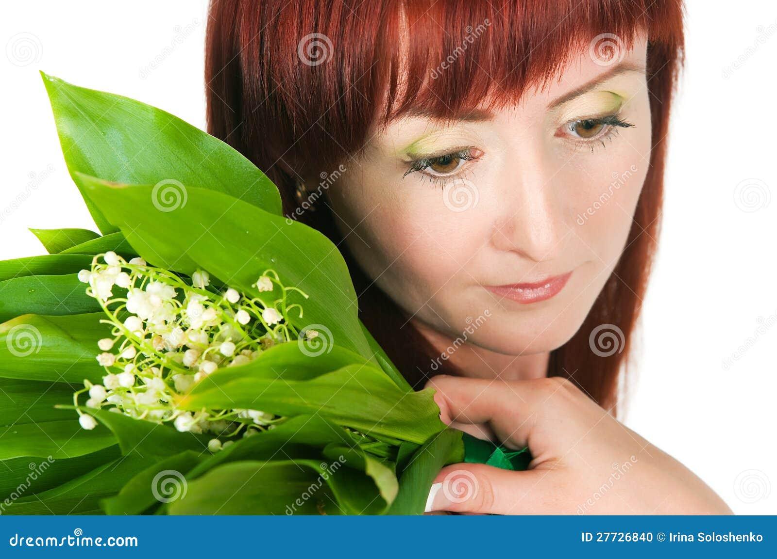 Das Mädchen mit einem Blumenstrauß der Lilien des Tales