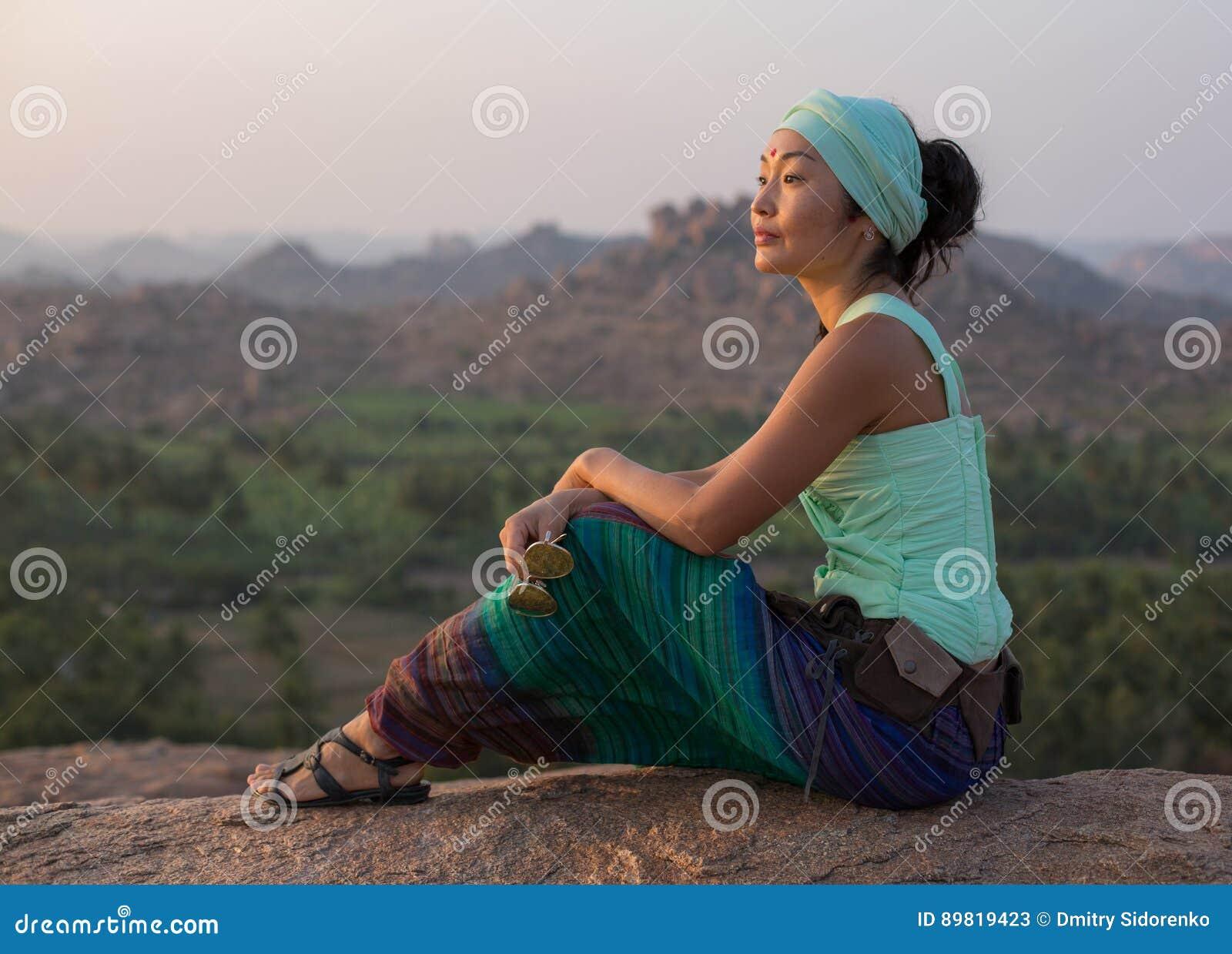 Das Mädchen sitzt auf einem Felsen und bewundert die steinige Landschaft bei Sonnenuntergang