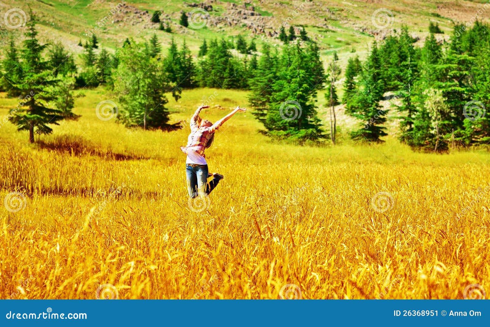 Das Mädchen springend auf Weizenfeld