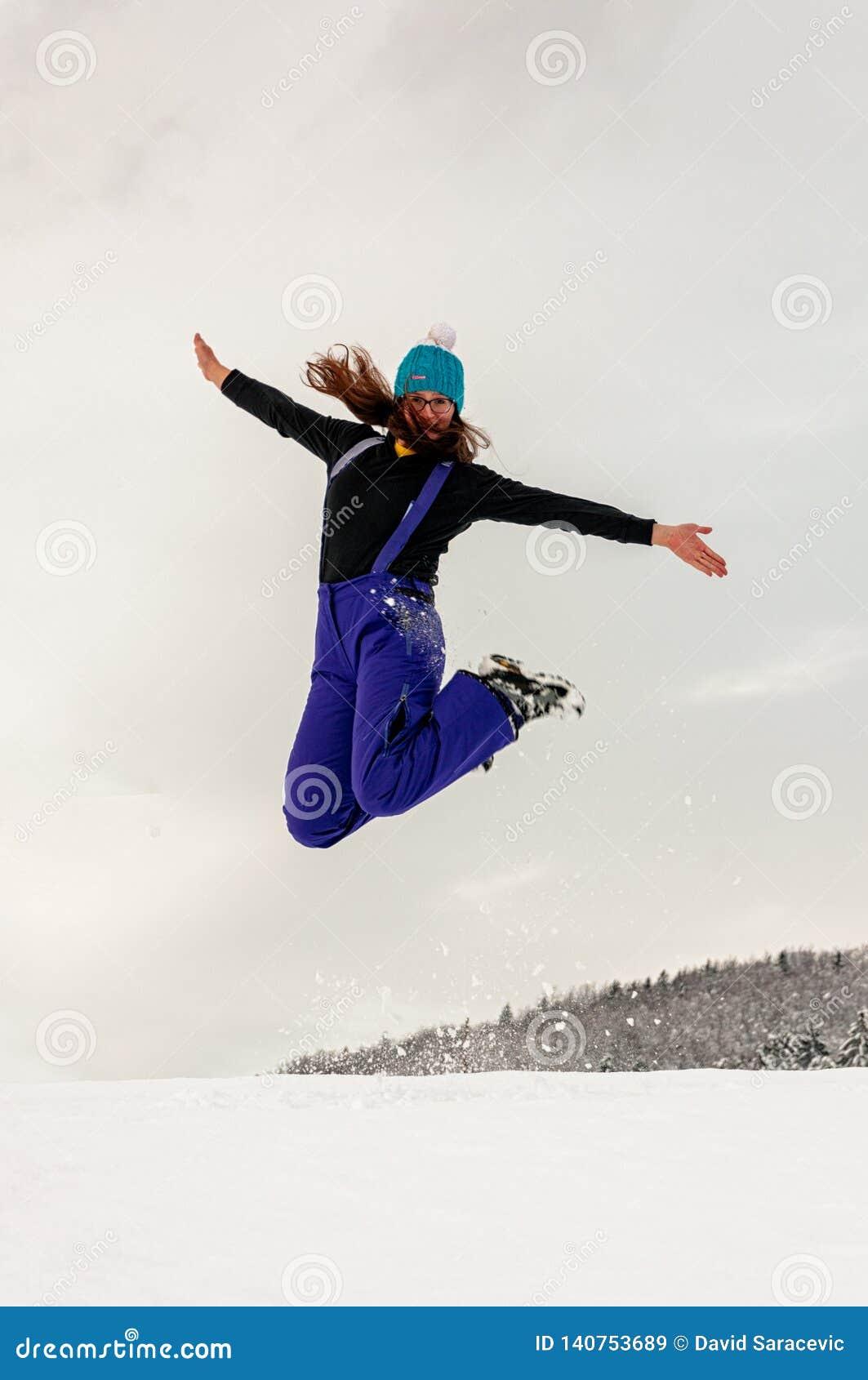 Das Mädchen springend in Schnee