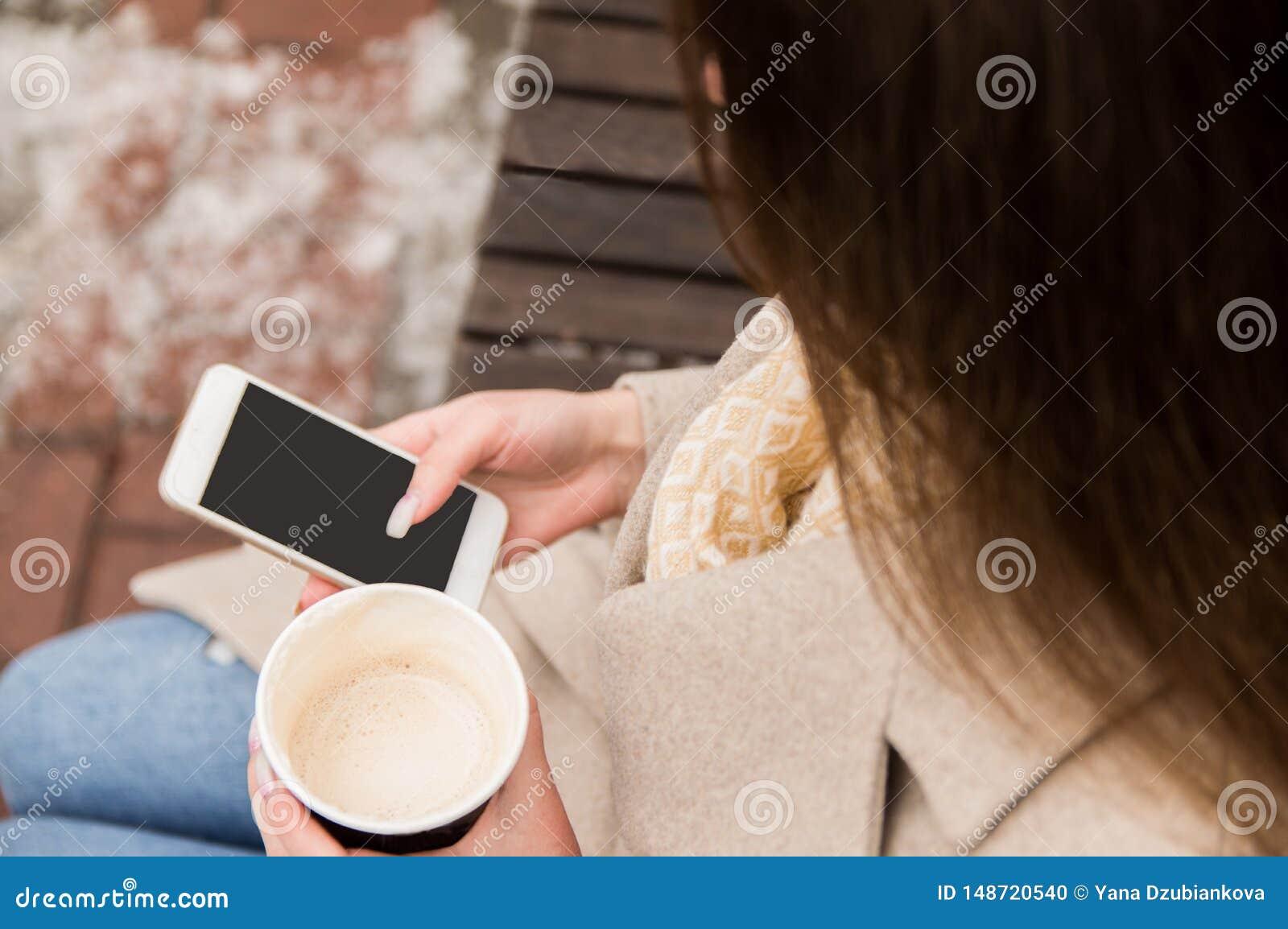 Das M?dchen, das auf der Stra?e mit einem Telefon und einem Kaffee in ihren H?nden, untersuchend das Telefon, auf einen Anruf war