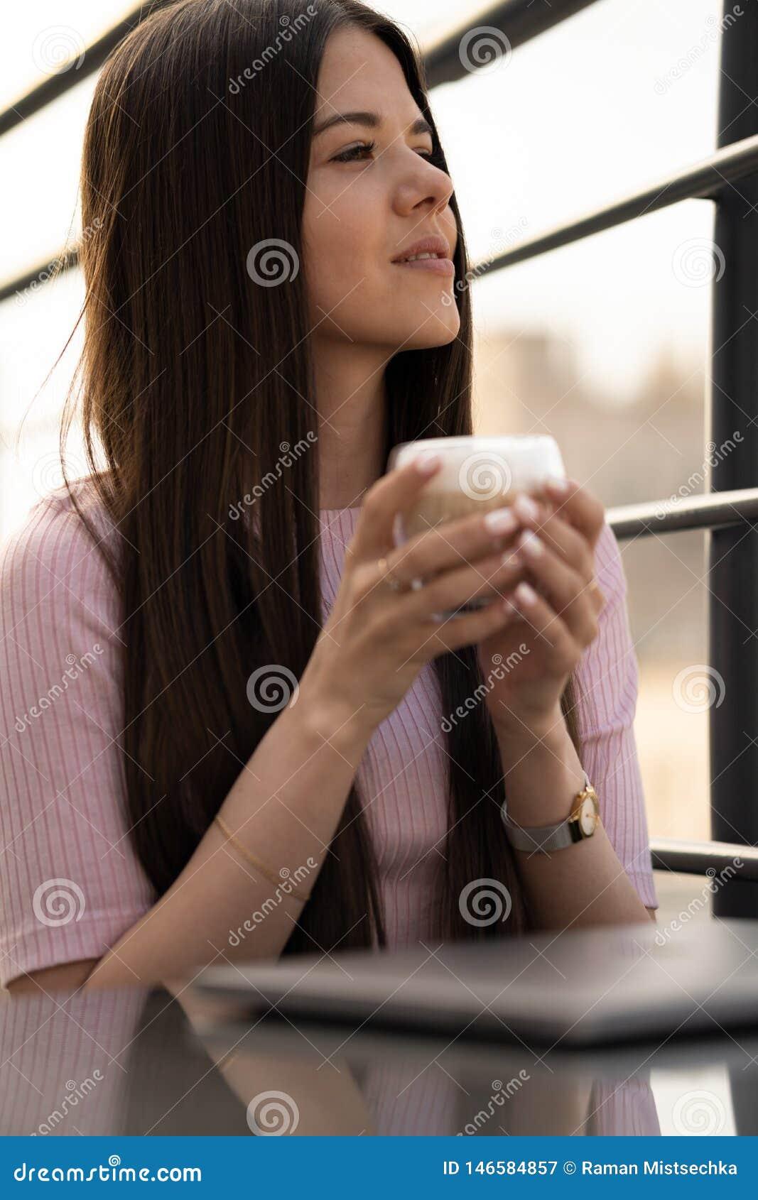 Das M?dchen genie?t Kaffee Ein Tasse Kaffee in den weiblichen H?nden Ist auf dem Tisch ein geschlossener Laptop