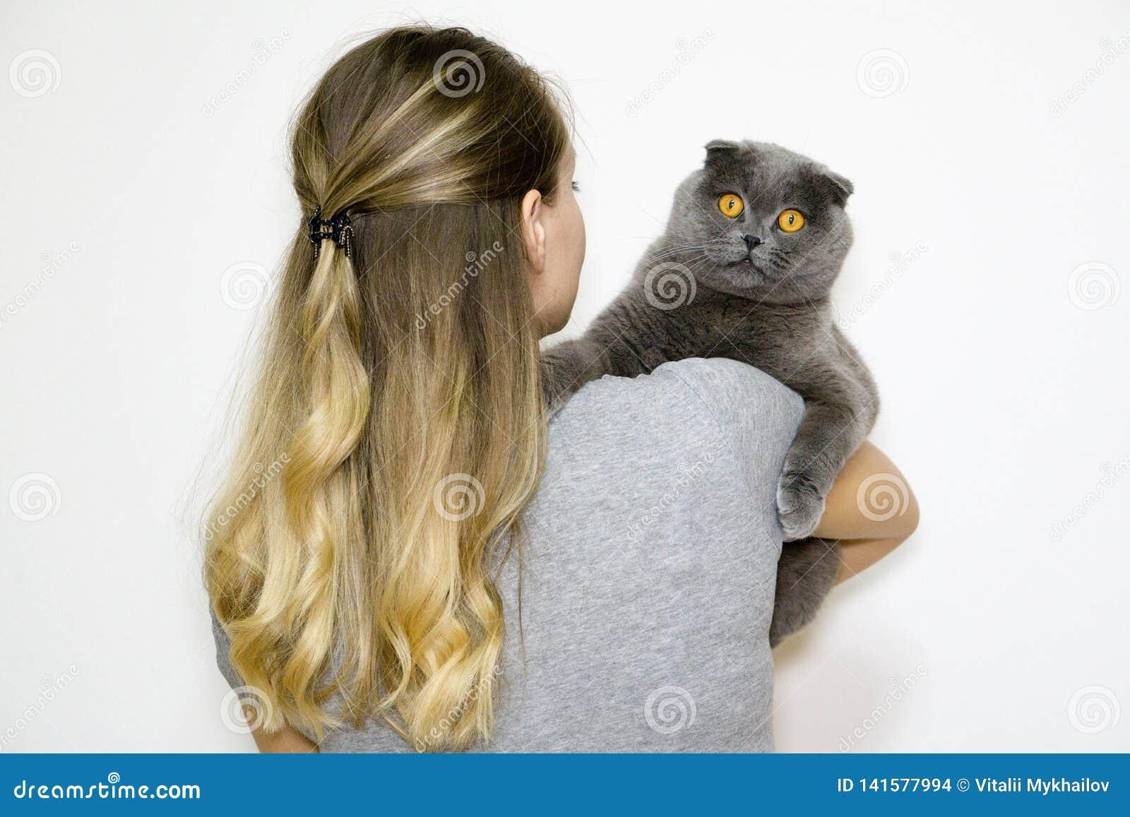 Das Modell ist zurück zu der Kamera und hält die Katze in seinen Armen rechts