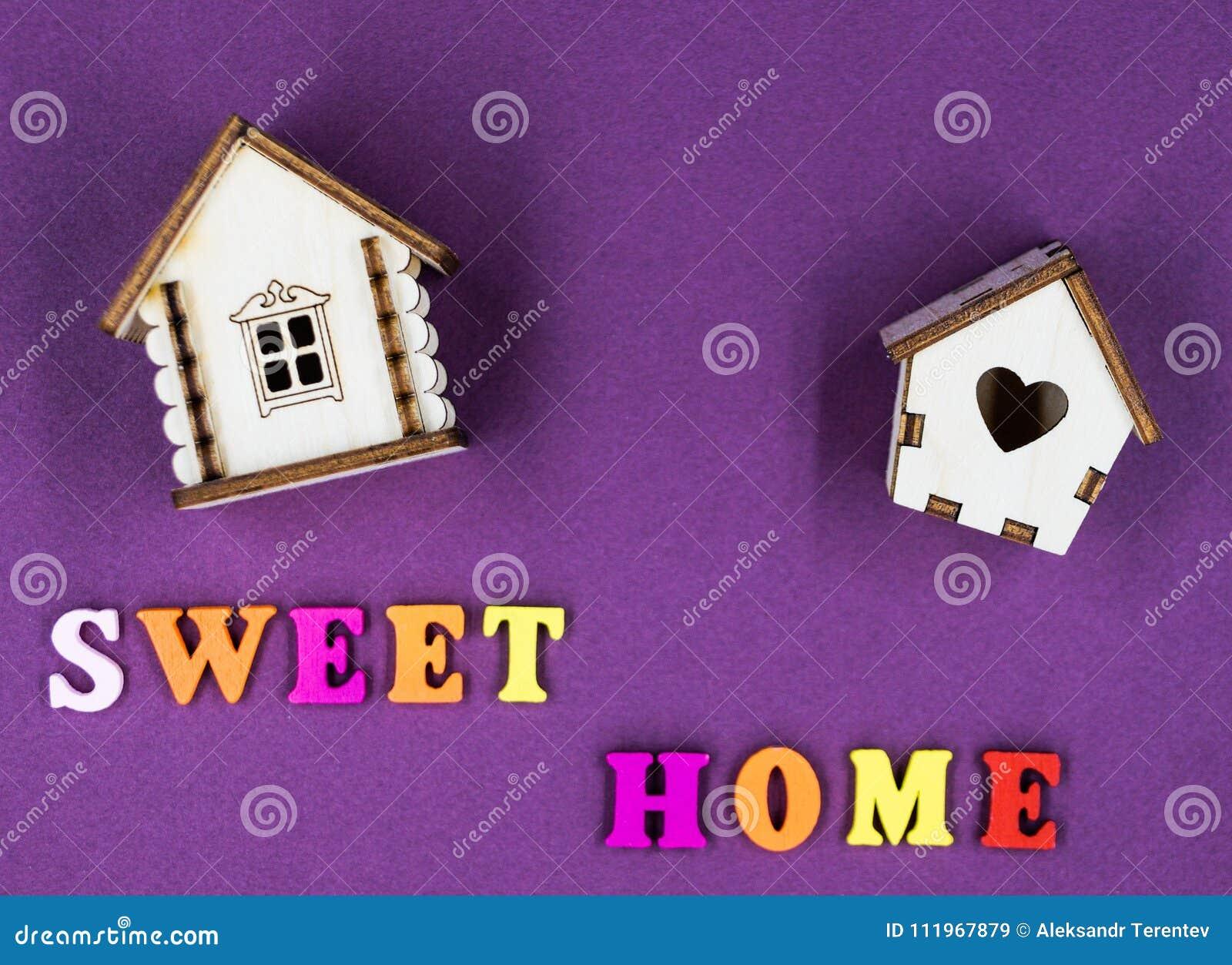 Das Phrase ` süße Haupt-` ausgebreitet auf einem rosa Hintergrund mit zwei Spielzeugholzhäusern