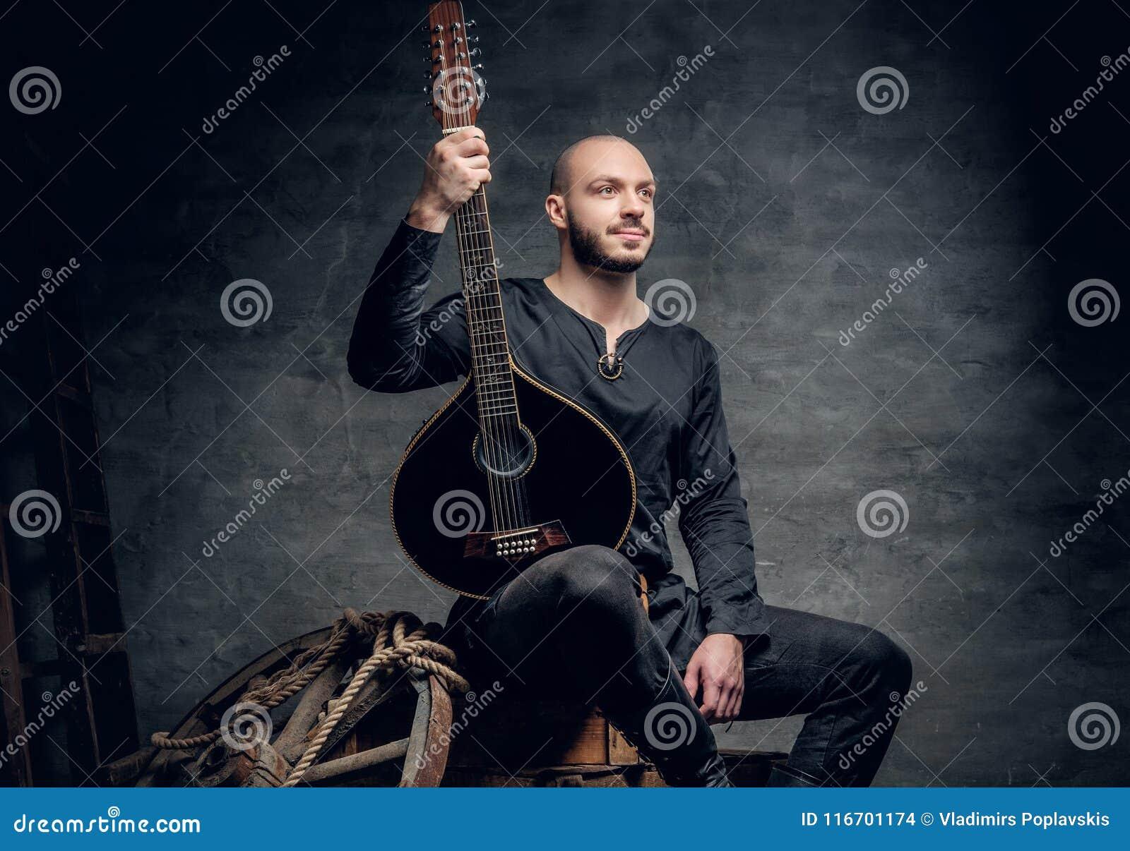 Das Porträt des Musikers gekleidet in der alten keltischen Kleidung sitzt auf einer Holzkiste und der Ausführung der alten Mandol