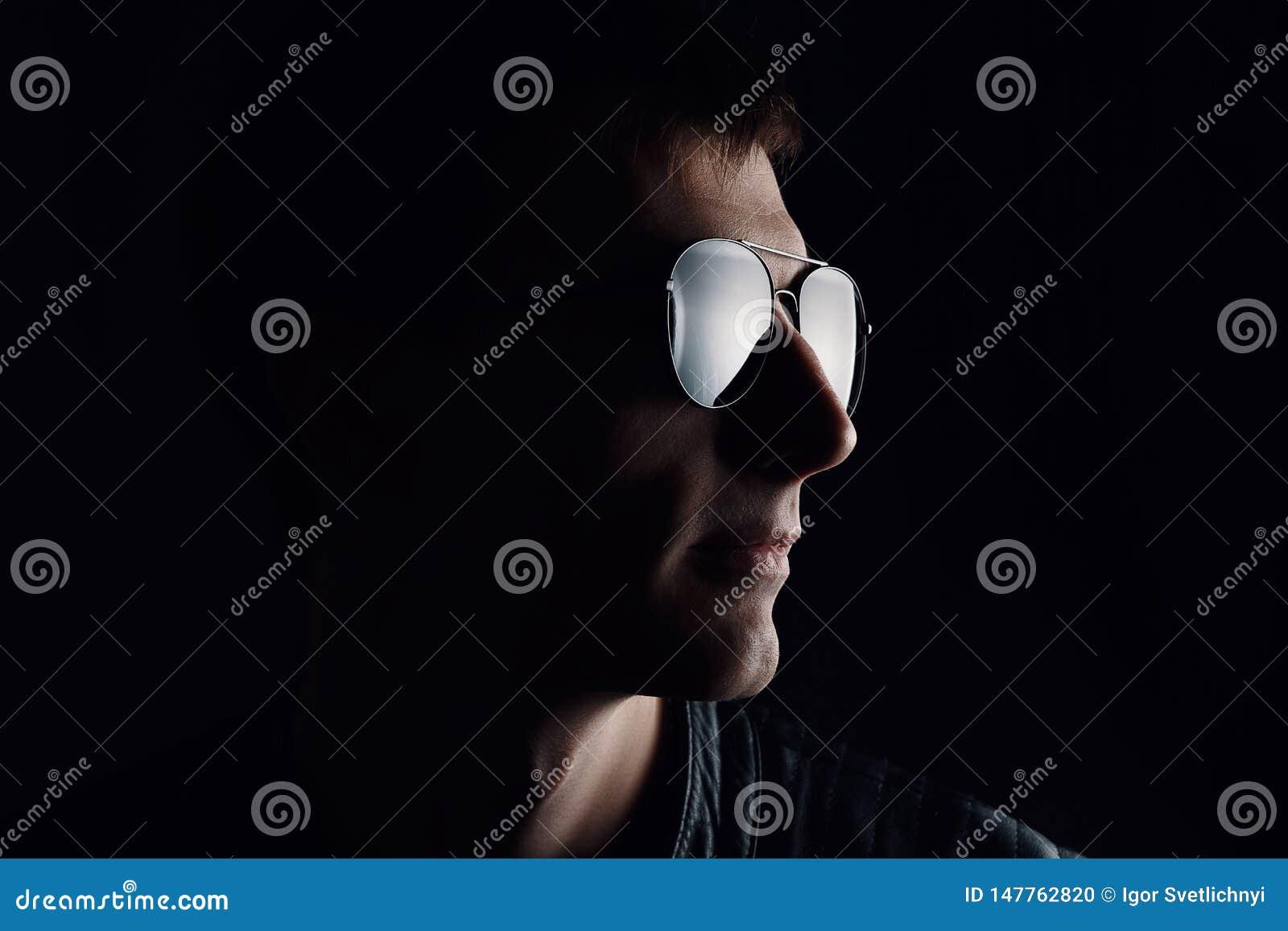 Das Portr?t des Jungemannes Nahaufnahme des ernsten jungen Mannes in einer schwarzen Lederjacke und in der Sonnenbrille