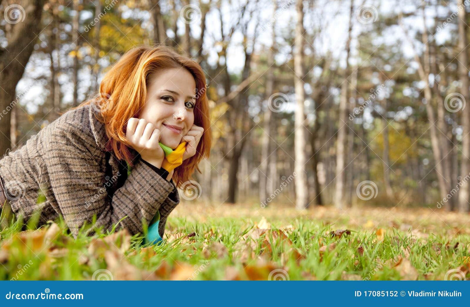 Das red-haired Mädchen in den Herbstblättern.
