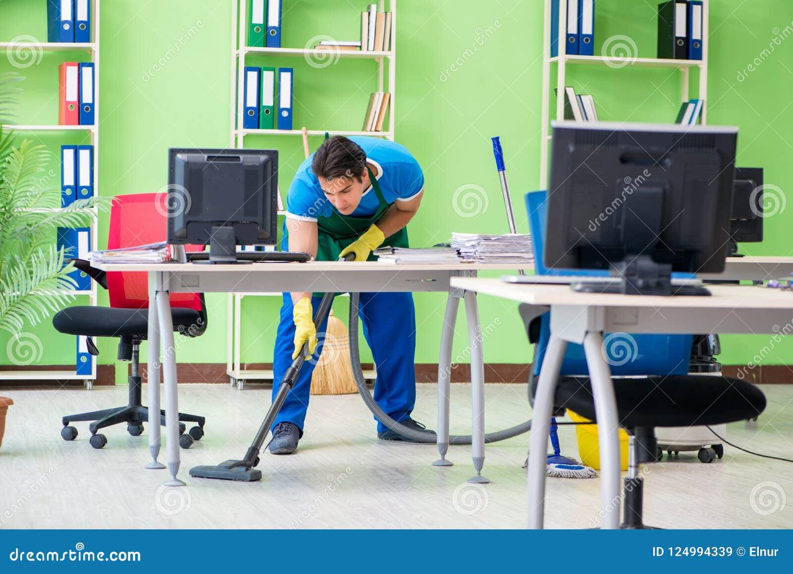 Das Reinigungsbüro des gutaussehenden Mannes mit Staubsauger