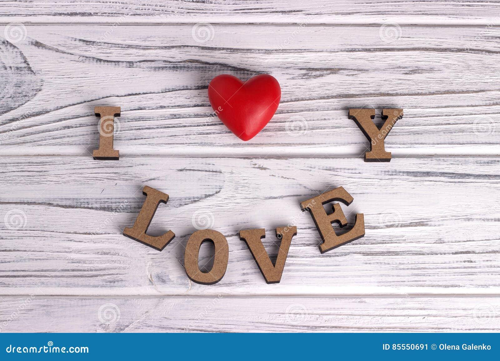Das rote Herz, das am Weiß hängt, malte rustikalen hölzernen Hintergrund mit ich liebe dich beschriften