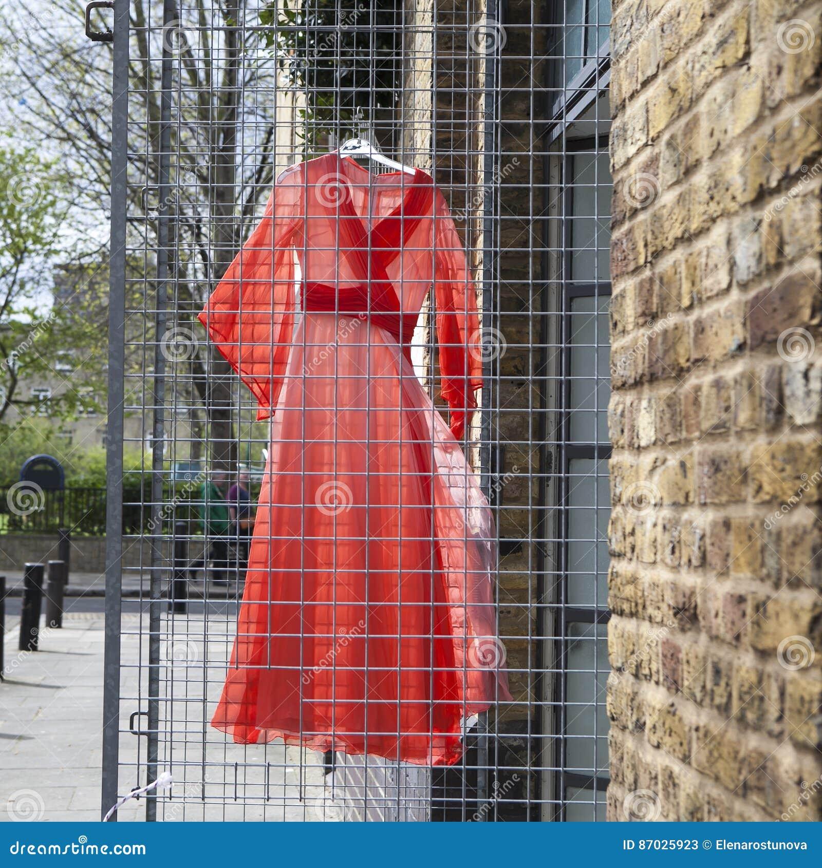 56eeb06c5e1d Das rote Kleid, das an einem Drahtgitter für Weinleseshop ungefähr  verkaufen hängt