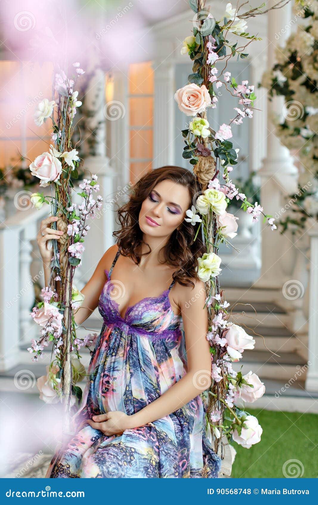 Das schöne Brunettemädchen, welches auf das Baby im purpurroten Kleid wartet, sitzen