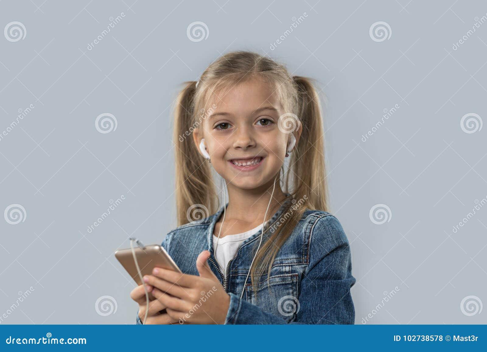 Das schöne kleine Mädchen, das Zellintelligentes Telefon verwendet, hören das Musik-Abnutzungs-Kopfhörer-glückliche Lächeln lokal