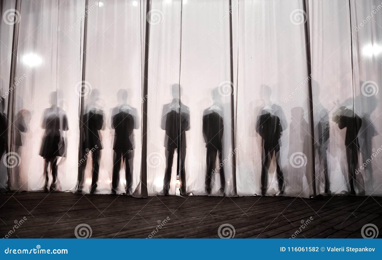 Das Schattenbild der Männer hinter dem Vorhang im Theater auf Stadium, der Schatten ist hinter den Kulissen dem Weiß und dem bla