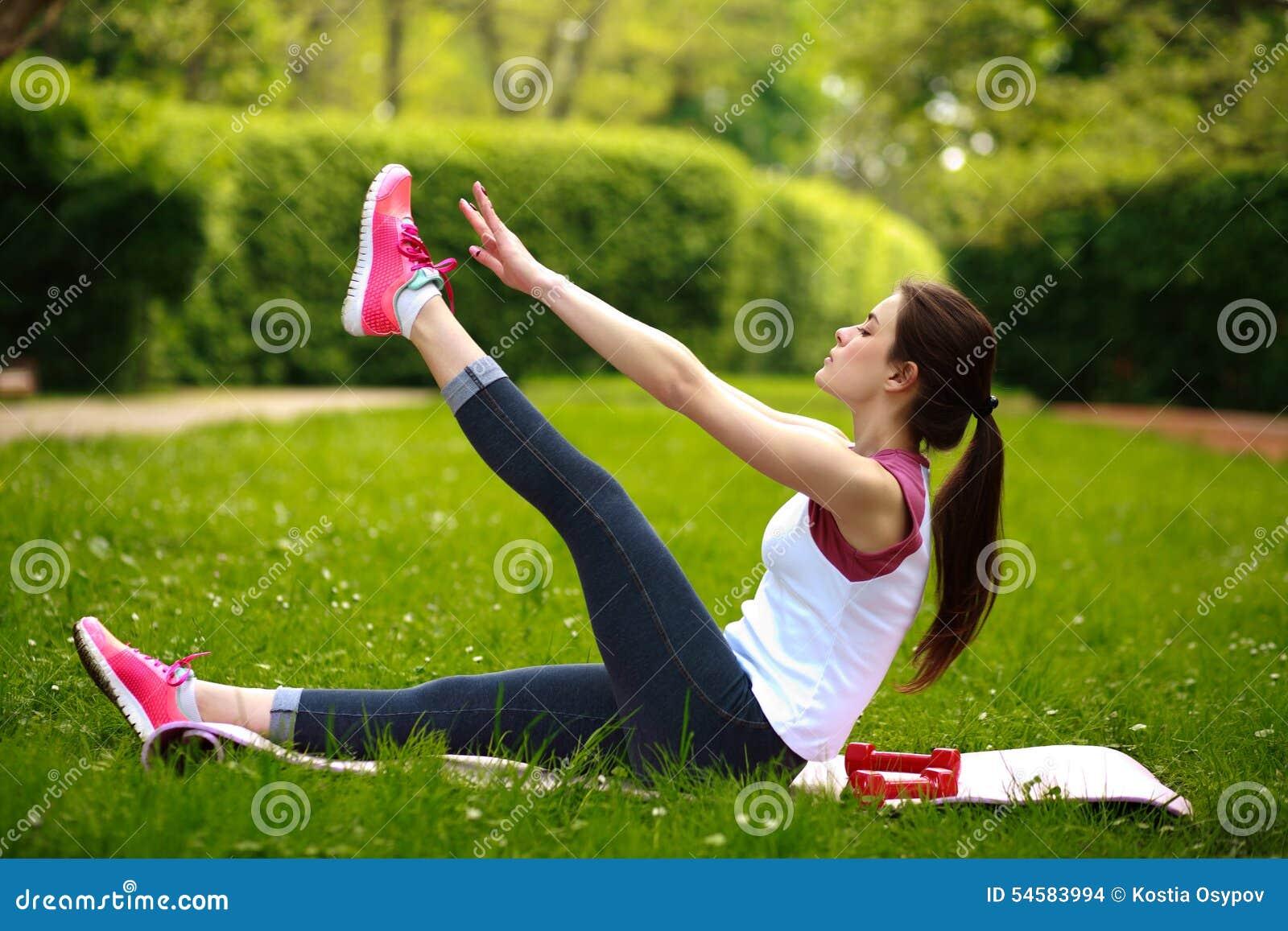 Das sportive Ausdehnen der jungen Frau, Eignung tuend trainiert im Park
