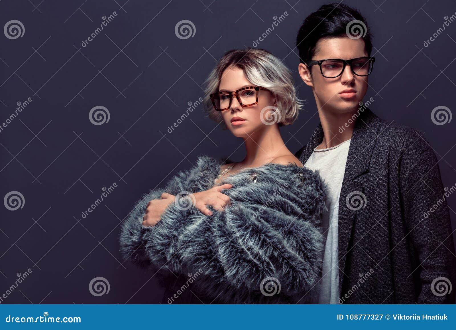 Das Studiotrieb des jungen Mannes und der Frau, das auf grauer Wand lokalisiert wird, arbeiten Fachmann um
