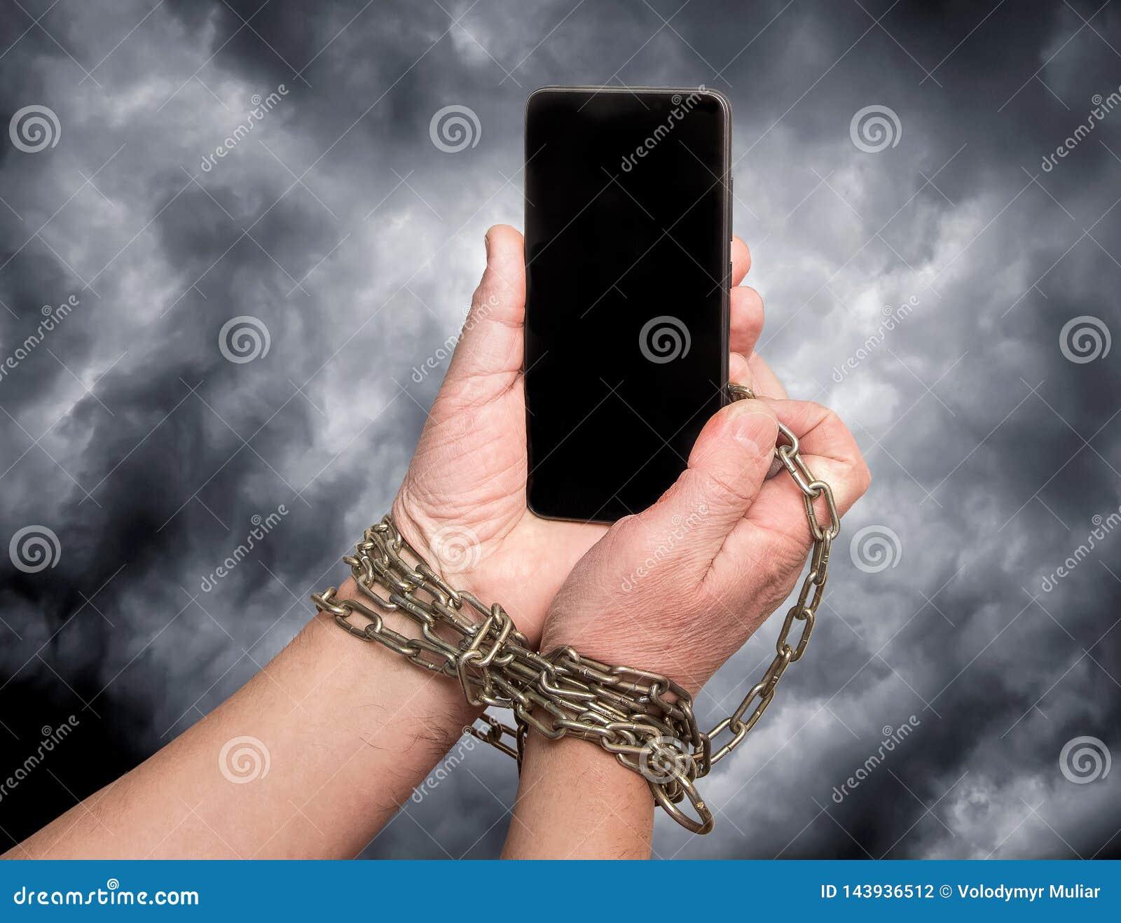 Das Telefon wird an die Hände auf dem dunklen drastischen Himmel des Hintergrundes angekettet Abhängigkeit auf beweglichem phone_