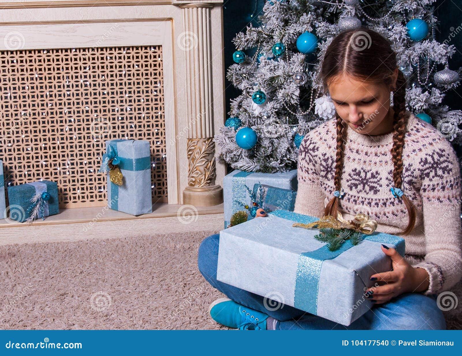 Das Weibliche Kind, Das Weihnachtsgeschenk In Den Händen Nahe Hält ...