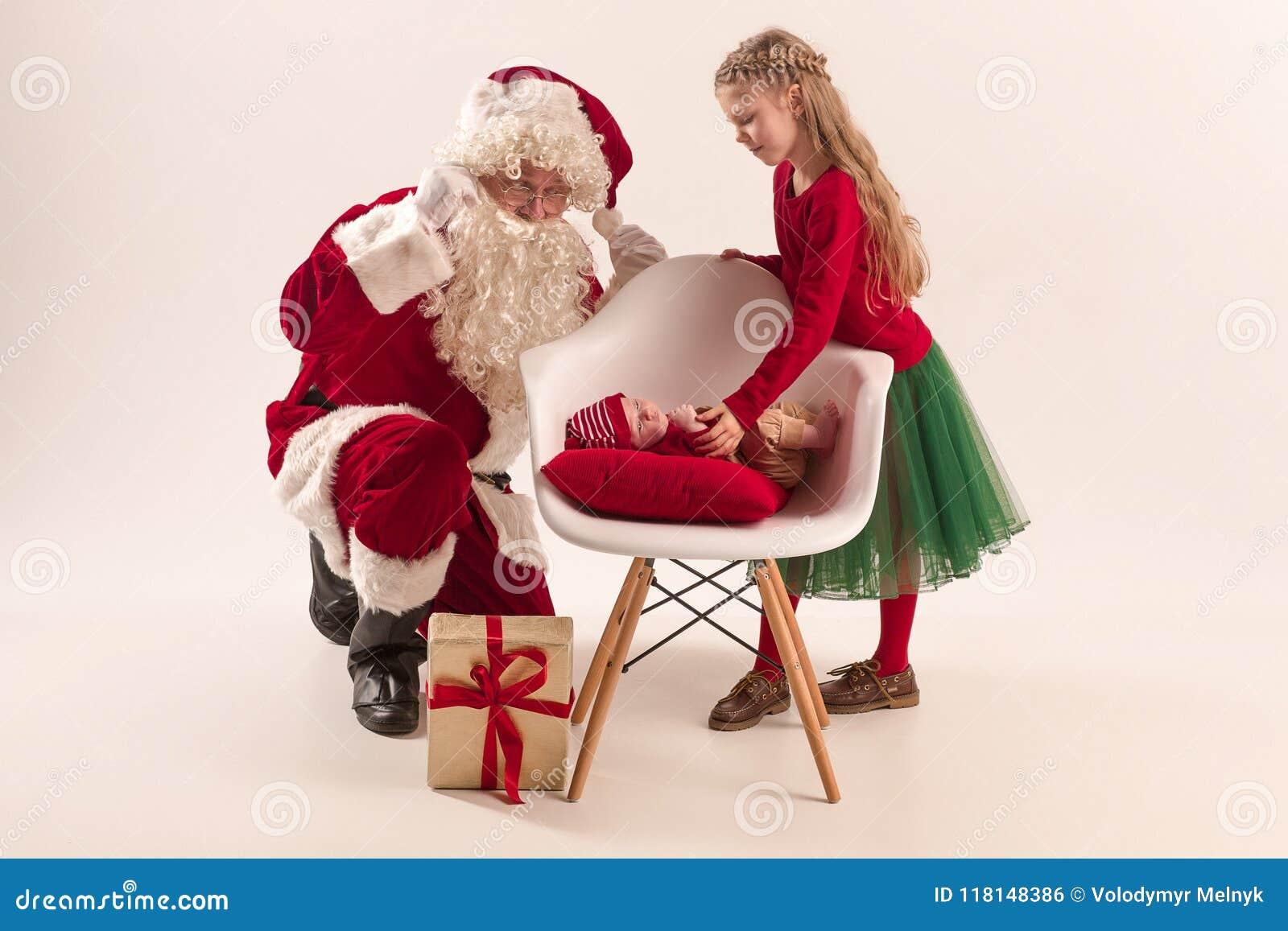 Das Weihnachtsporträt des netten kleinen neugeborenen Babys, gekleidet im Weihnachten kleidet, Atelieraufnahme, Winterzeit