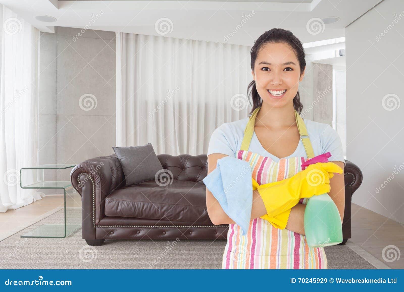 Das zusammengesetzte Bild der Frau stehend mit den Armen kreuzte das Halten von Reinigungsprodukten