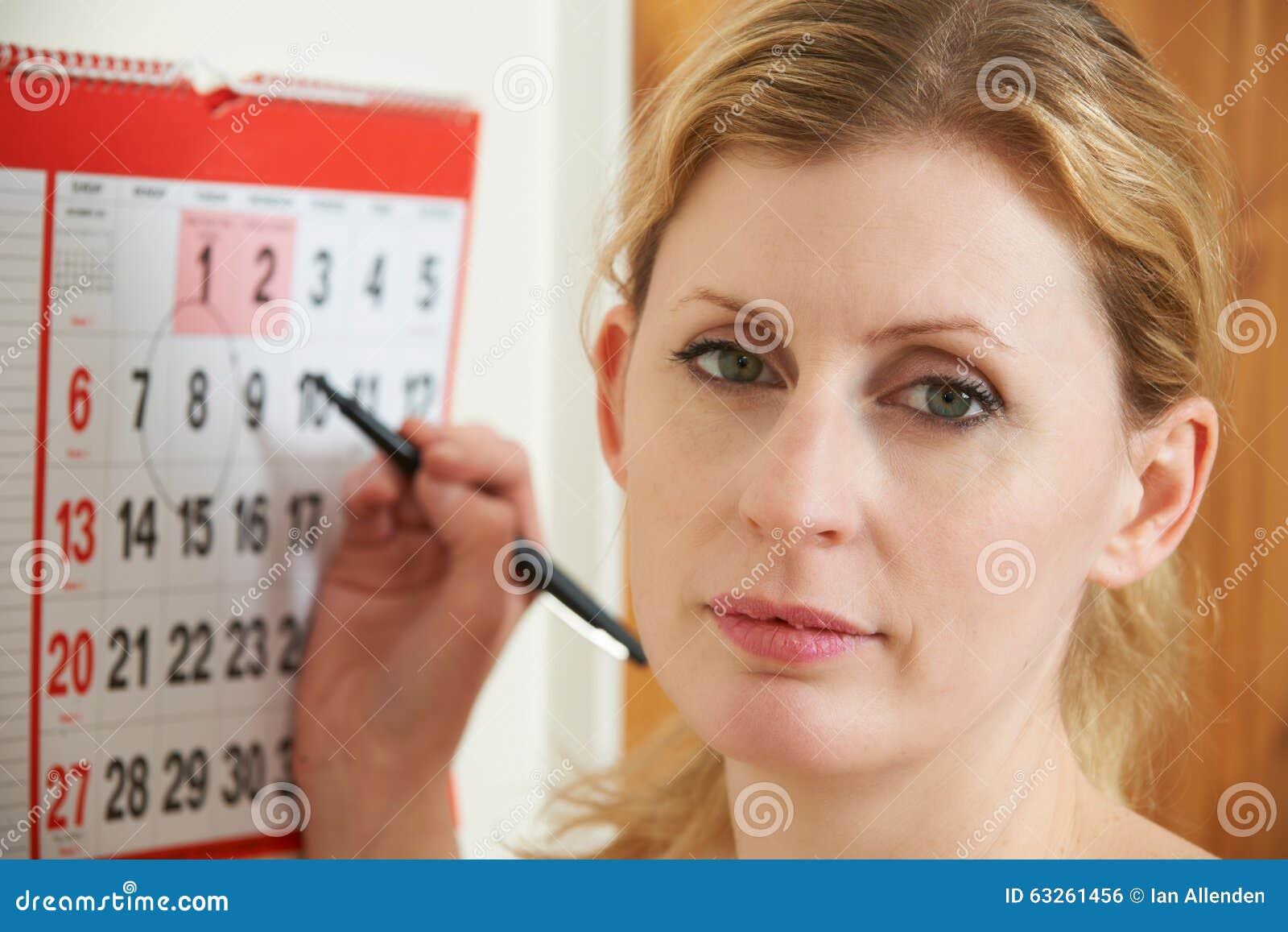 Data de circundamento preocupada da mulher no calendário