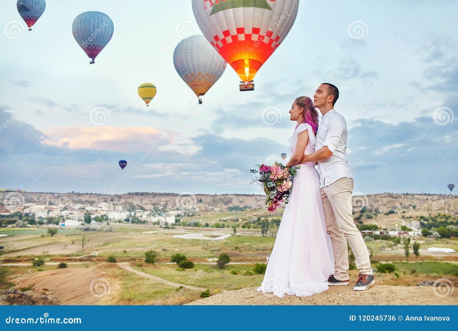 Data para w miłości przy zmierzchem przeciw tłu balony w Cappadocia, Turcja Mężczyzna i kobiety przytulenia pozycja na wzgórzu