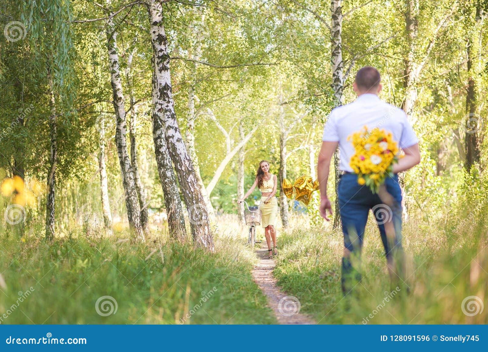 Data w lasu A mężczyzna z kwiatami z powrotem czeka kobiety na bicyklu jego