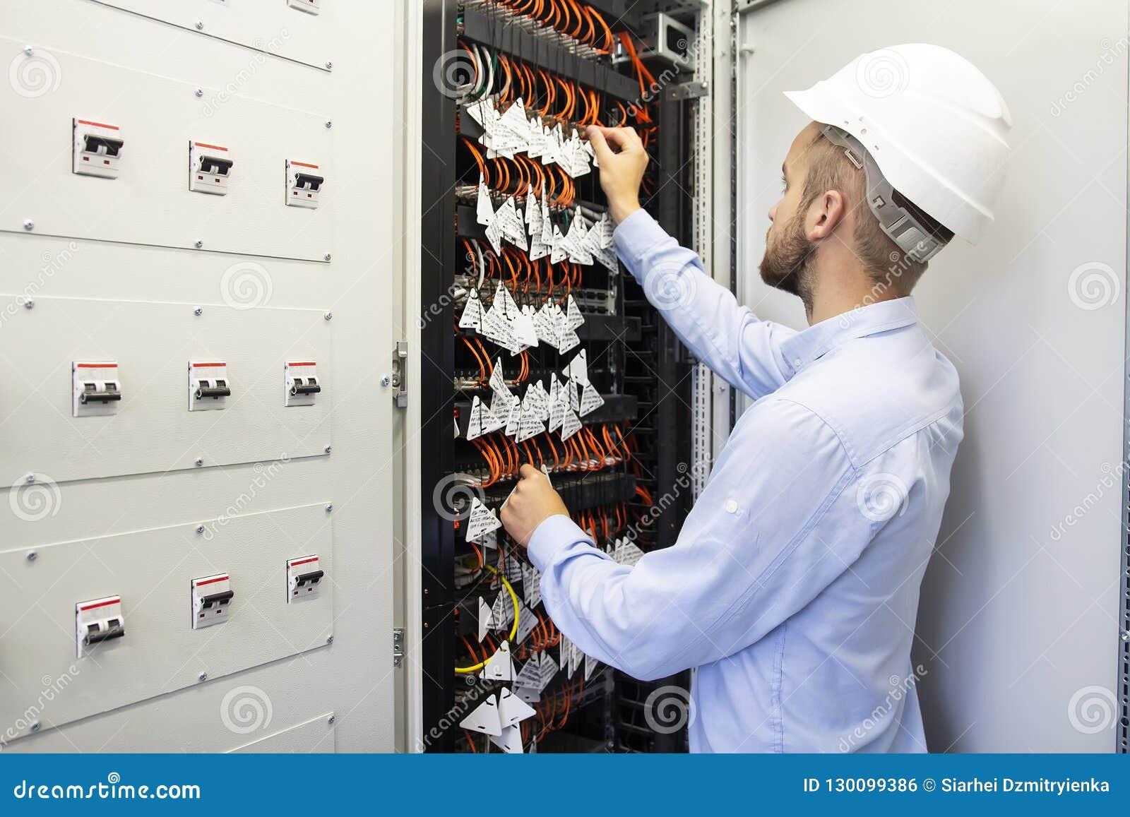 Datacenter的技术员工程师 连接光纤的网络技术员在服务器室