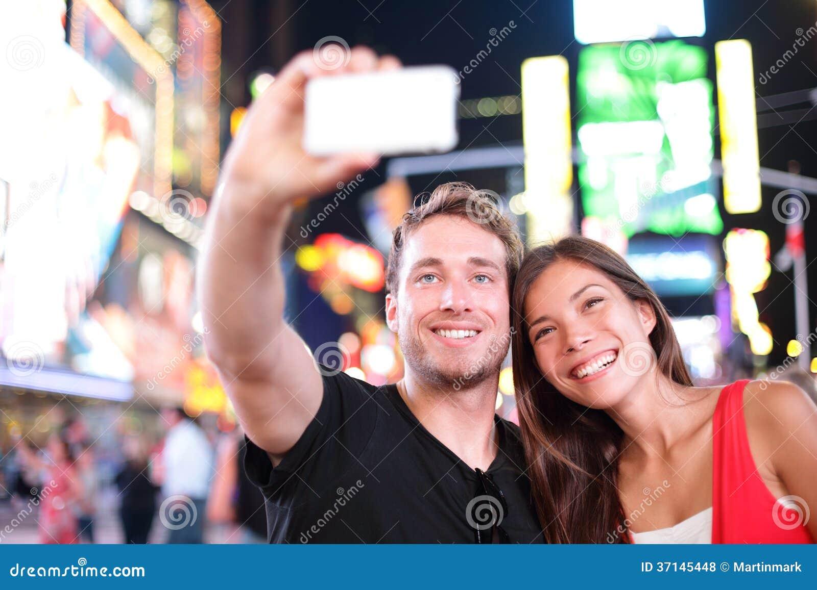 Datando os pares novos felizes no amor que toma a foto do selfie no Times Square, New York City na noite. Turista multirracial nov