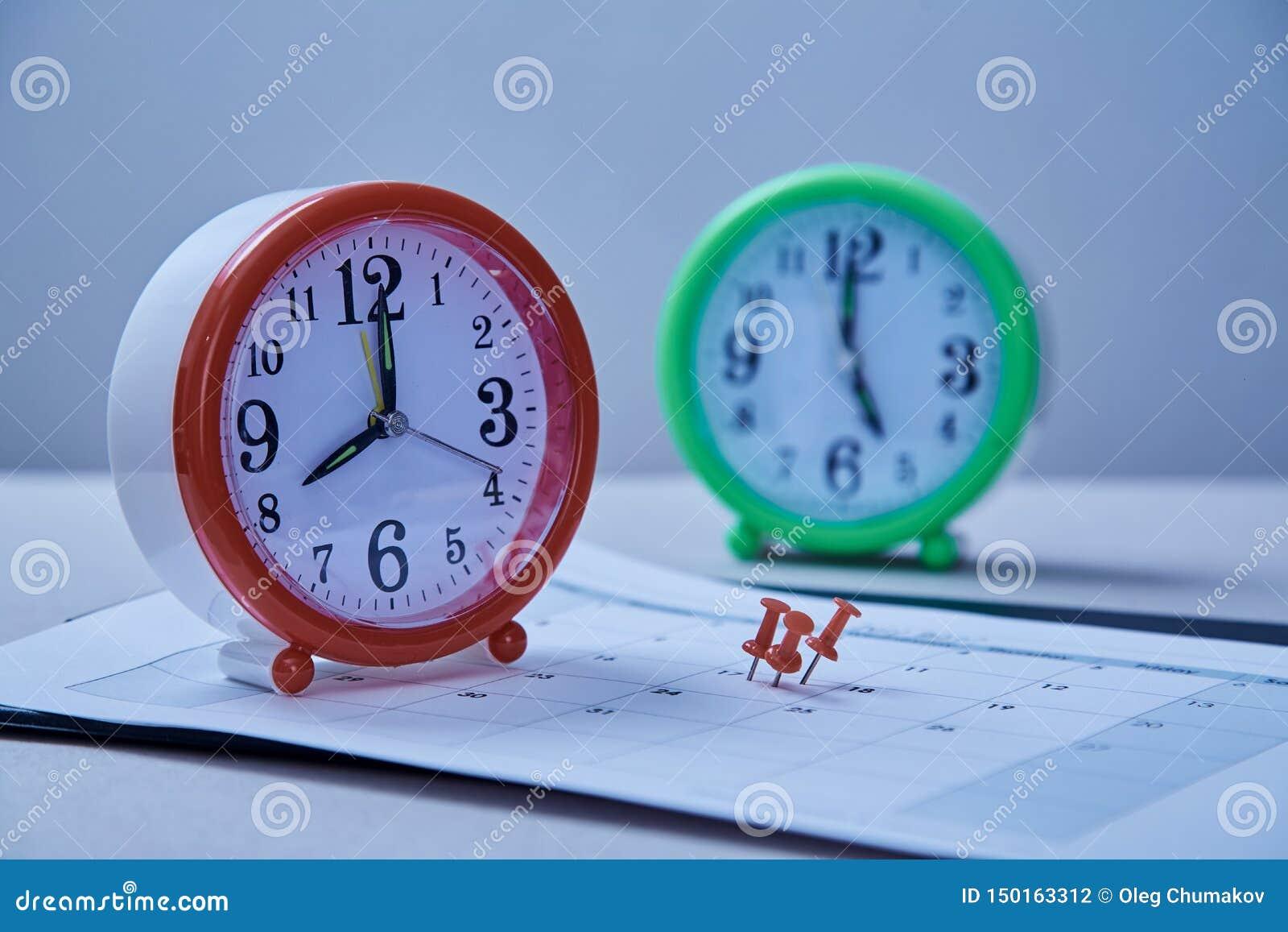 Date-butoir de gestion du temps et concept de programme : autocollants collés sur l horloge de table et la punaise rouge