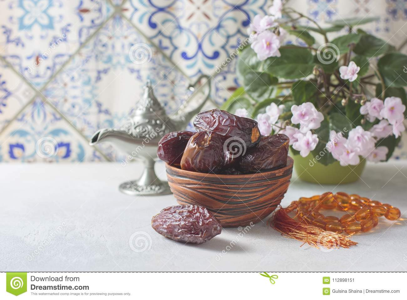 Dates fruit and rosary still life.